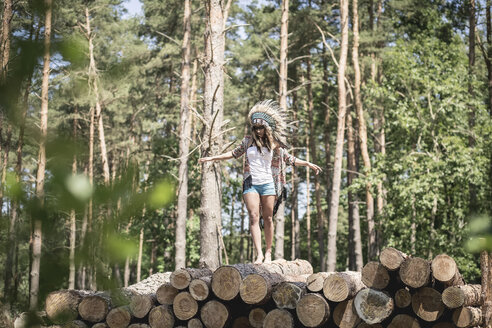 Young woman masquerade as an Indian balancing on stack of wood - ASCF000207