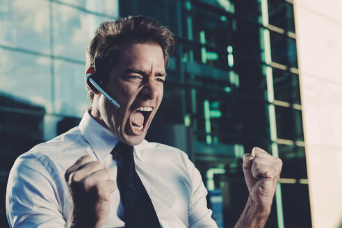 Excited businessman with clenched fists screaming outside office building - CHAF000413