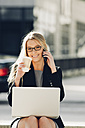 Businesswoman with coffee to go using laptop and cell phone - CHAF000548
