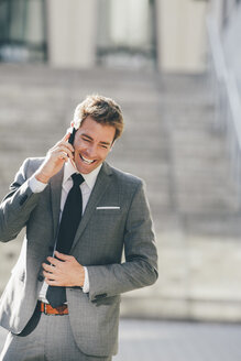 Smiling businessman talking on cell phone outdoors - CHAF000553