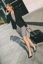 Businesswoman on cell phone walking with suitcase - CHAF000555