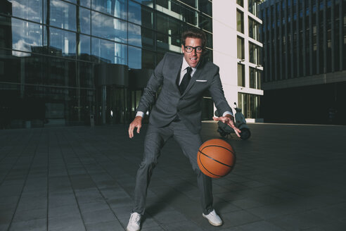 Businessman playing basketball outside office building - CHAF000439