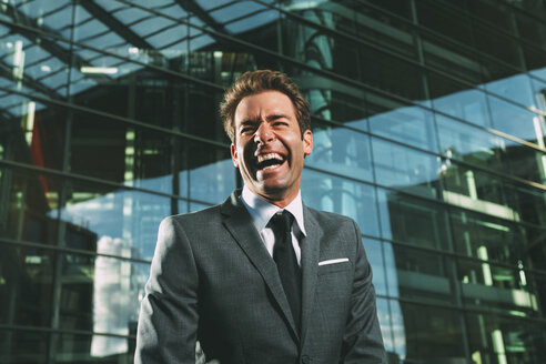 Laughing businessman outside office building - CHAF000441