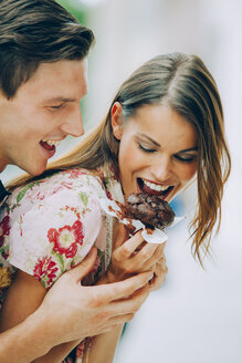 Happy young couple eating chocolate muffin - CHAF000452