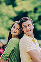 Smiling young couple back to back outdoors - CHAF000460