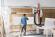 Carpenter cutting wood in workshop with machine - JUBF000045