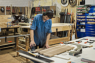 Carpenter using grinding machine in workshop - JUBF000024