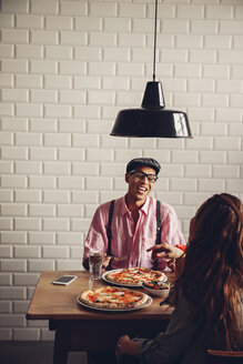 Young couple eating pizza in restaurant - CHAF001283