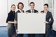 Portrait of happy business team holding a blank billboard while at office - CHAF000482