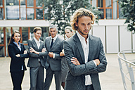 Businessman with crossed arms, excluded from group of business people - CHAF000495