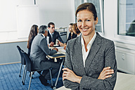 Mature businesswoman sitting on desk with arms crossed, team working in background - CHAF000510