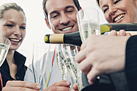 Business team drinking champagne and celebrating success in office - CHAF001325