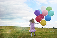 Little girl with balloons running on a meadow - STKF001317