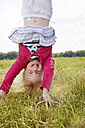 Portrait of happy little girl doing handstand on a meadow - STKF001323