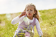 Portrait of little girl blowing soap bubbles on a meadow - STKF001332