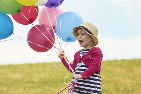 Little girl with balloons on a meadow - STKF001350
