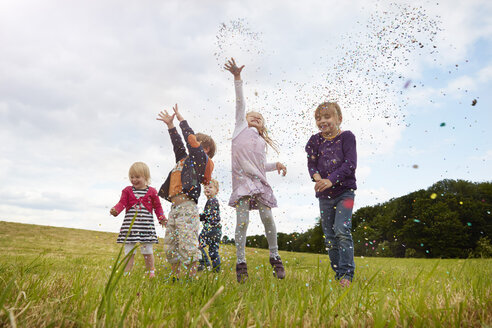 Five little children throwing confetti on a meadow - STKF001356