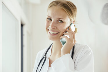 Smiling female doctor talking on cell phone - MFF001824