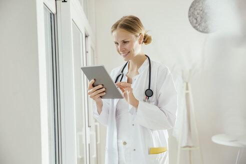 Smiling female doctor using digital tablet - MFF001826