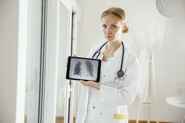 Portrait of serious female doctor showing an x-ray on digital tablet - MFF001828