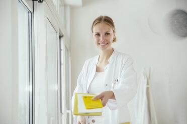 Portrait of smiling female doctor handing over medical documents - MFF001830
