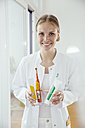 Portrait of smiling female dentist holding toothbrush and toothpaste for children and adults - MFF001848