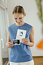 Smiling young woman holding ultrasound image and maternity log - MFF001844