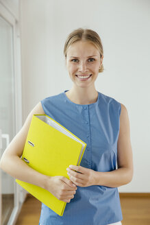 Smiling young woman holding a folder - MFF001845