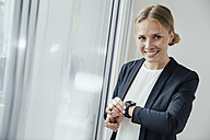 Smiling young businesswoman checking her smart watch - MFF001854