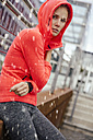 Young sporty woman sitting in rain - MFF001857
