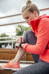 Young sporty woman checking her smart watch - MFF001858