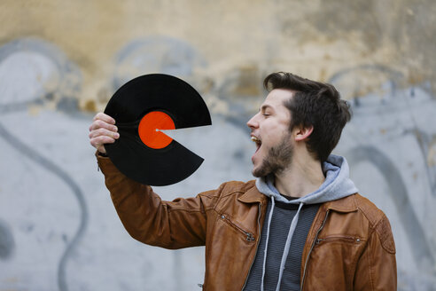 Young man holding broken record - HCF000124