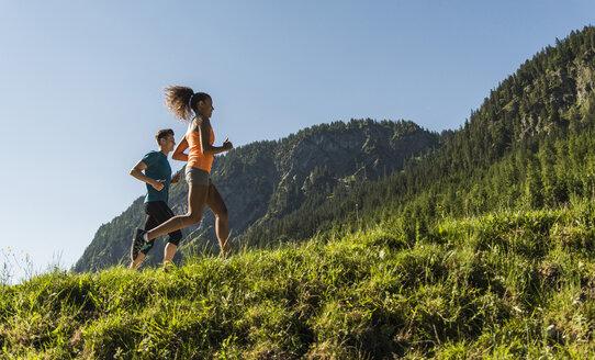 Austria, Tyrol, Tannheim Valley, young couple jogging in alpine landscape - UUF004920
