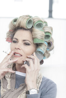 Portrait of woman with hair curlers smoking a cigarette while talking on phone - ZEF006296