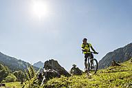Austria, Tyrol, Tannheim Valley, young man on mountain bike in alpine landscape - UUF004945