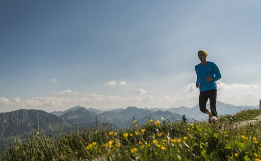 Austria, Tyrol, Tannheim Valley, young man jogging in mountains - UUF004984