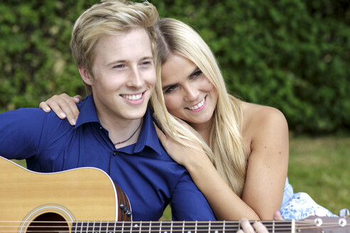Happy young couple with guitar in park - GDF000792