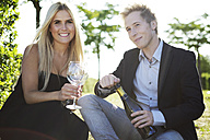 Elegant young couple outdoors drinking wine - GDF000803