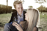 Elegant young couple outdoors drinking wine - GDF000805