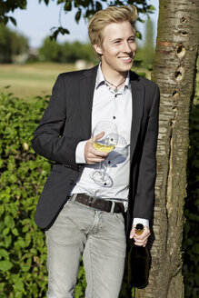 Smiling young man outdoors with wine glass and bottle - GDF000806
