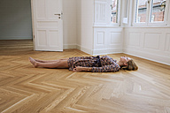 Young woman lying alone on floor in an empty room - CHAF000571