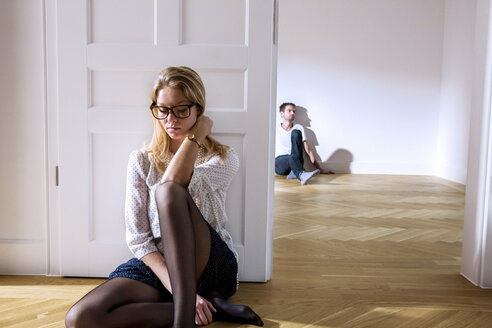 Pensive young woman in empty apartment with man in background - CHAF000577
