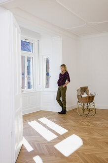 Young pregnant woman with pram in an empty room looking out of window - CHAF000586