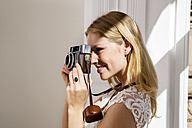 Smiling young woman taking picture with old camera - CHAF000597