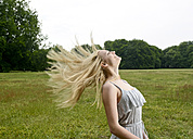 Young woman tossing her hair on a meadow - BFRF001318