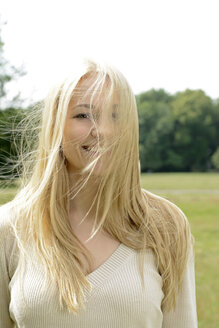 Portrait of smiling blond woman with blowing hair - BFRF001352