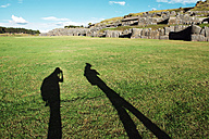 Peru, Cusco, shadow of two backpackers visiting Saksaywaman citadel - GEMF000282