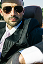 Portrait of businessman with sunglasses in a convertible car - ABZF000083