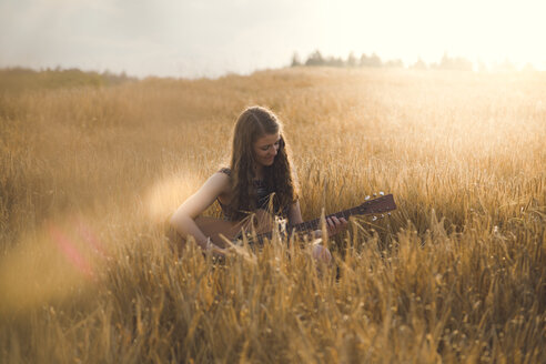 Young woman playing guitar in field in the evening - SARF002053