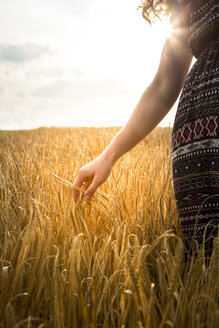 Young woman standing in barley field in the evening - SARF002039